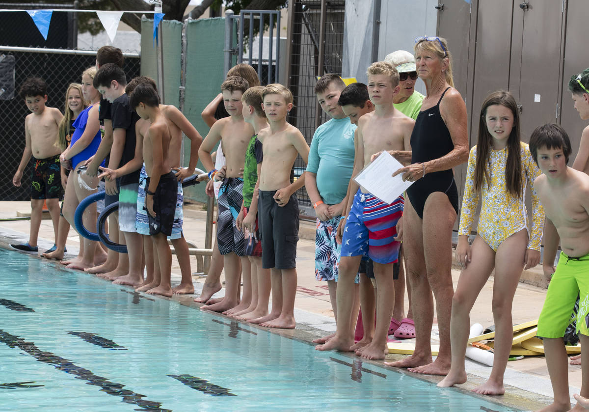Children gather around the swimming pool during the 12th annual World's Largest Swimming Lesson ...