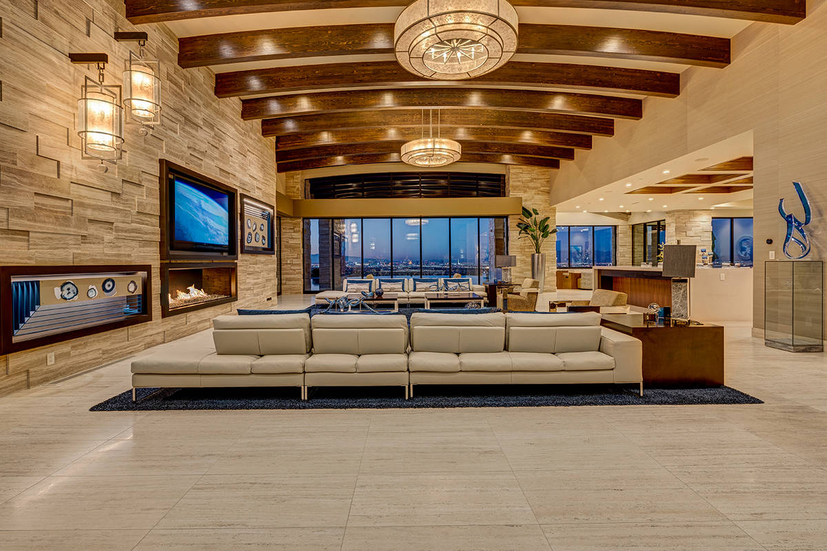 The living room features wooden beams, modern fireplace and access to the nearly 6,000-square-f ...