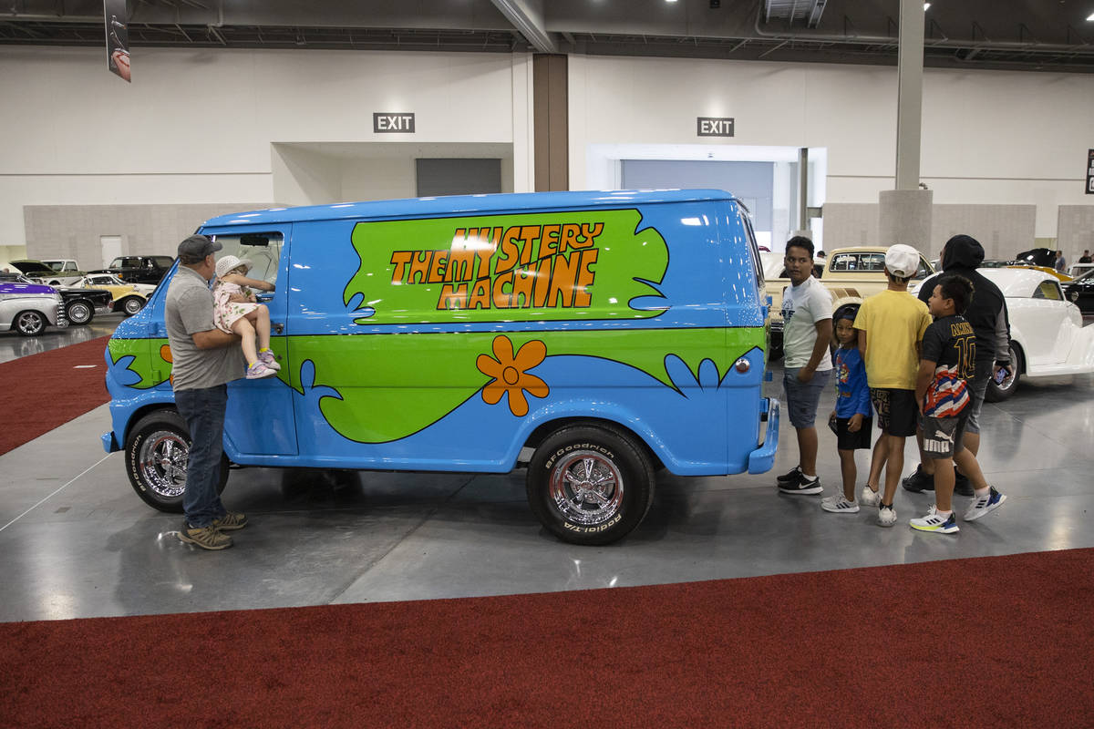 """People check out the 1968 For Ecoline """"Mystery Machine"""" van in the Barrett-Jackson au ..."""