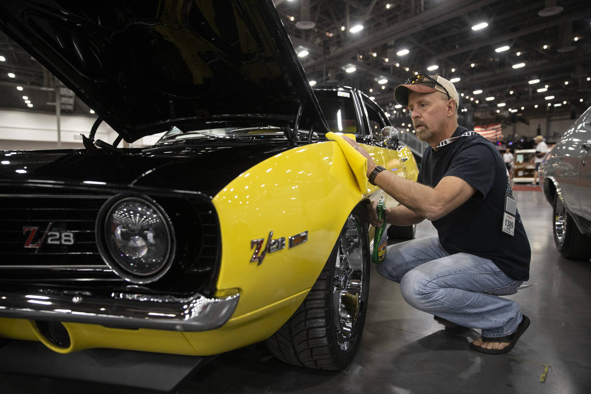 Dean Swan, of Idaho, polishes his 1969 Chevrolet Camaro custom coupe, showcased in the Barrett- ...