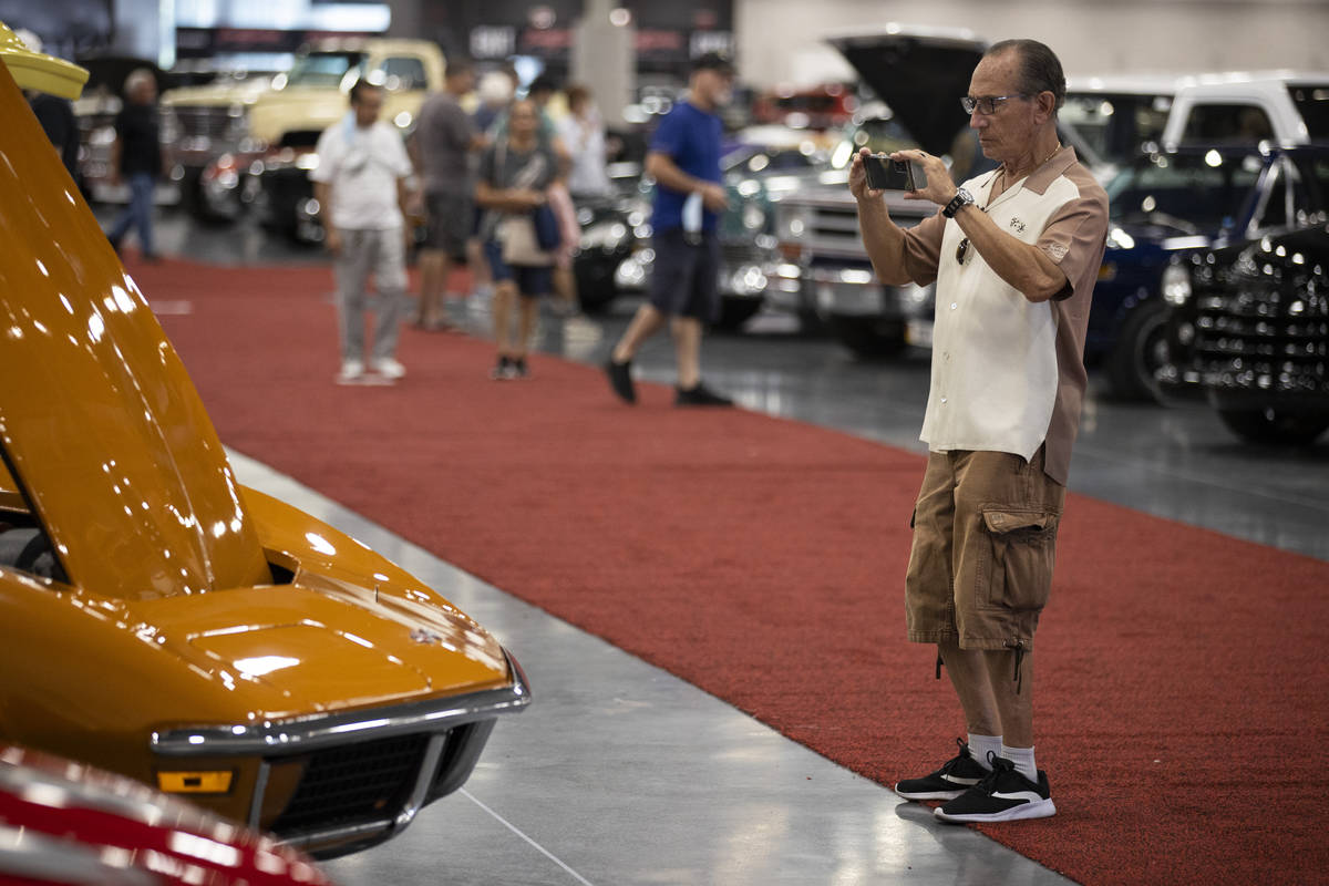 Erwin of Las Vegas, who declined to give a last name, takes photos in the showroom floor while ...