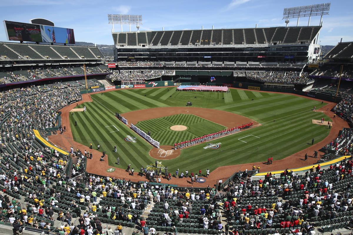 FILE - The Los Angeles Angels and Oakland Athletics stand for the national anthem at the Oaklan ...