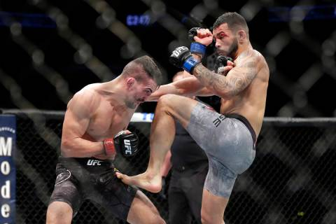 Mirsad Bektic, left, punches as Dan Ige, right, throws a knee during a featherweight mixed mart ...