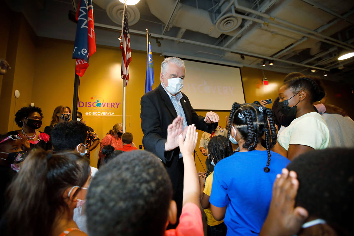 Nevada. Gov. Steve Sisolak high-fives children during a Juneteenth celebration at the Discovery ...