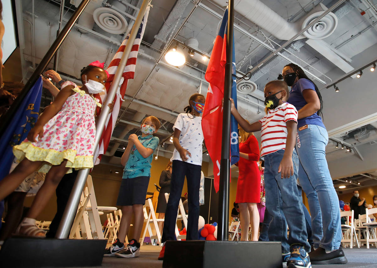 Jacobi Holmes, 4 of Las Vegas, right, touches a Juneteenth flag with other children before a Ju ...