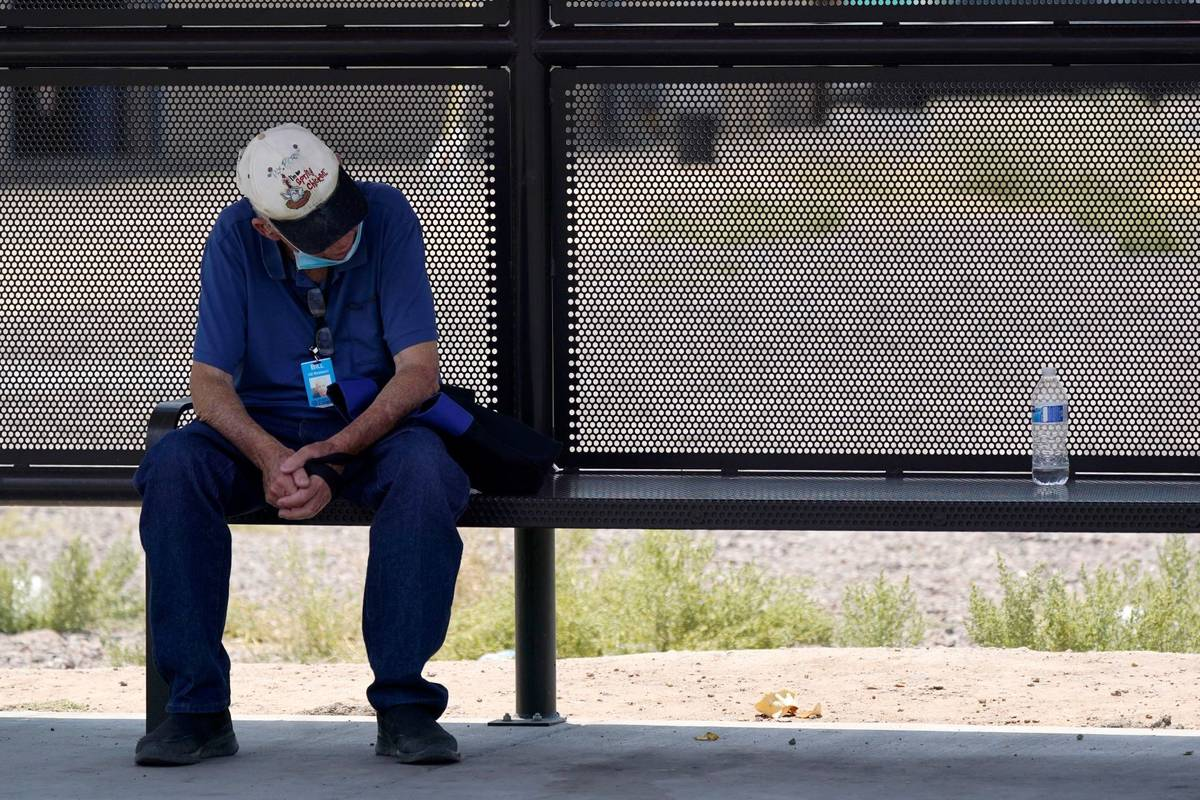 A person waits for a bus in the shade as the heat wave in the Western states continues Thursday ...