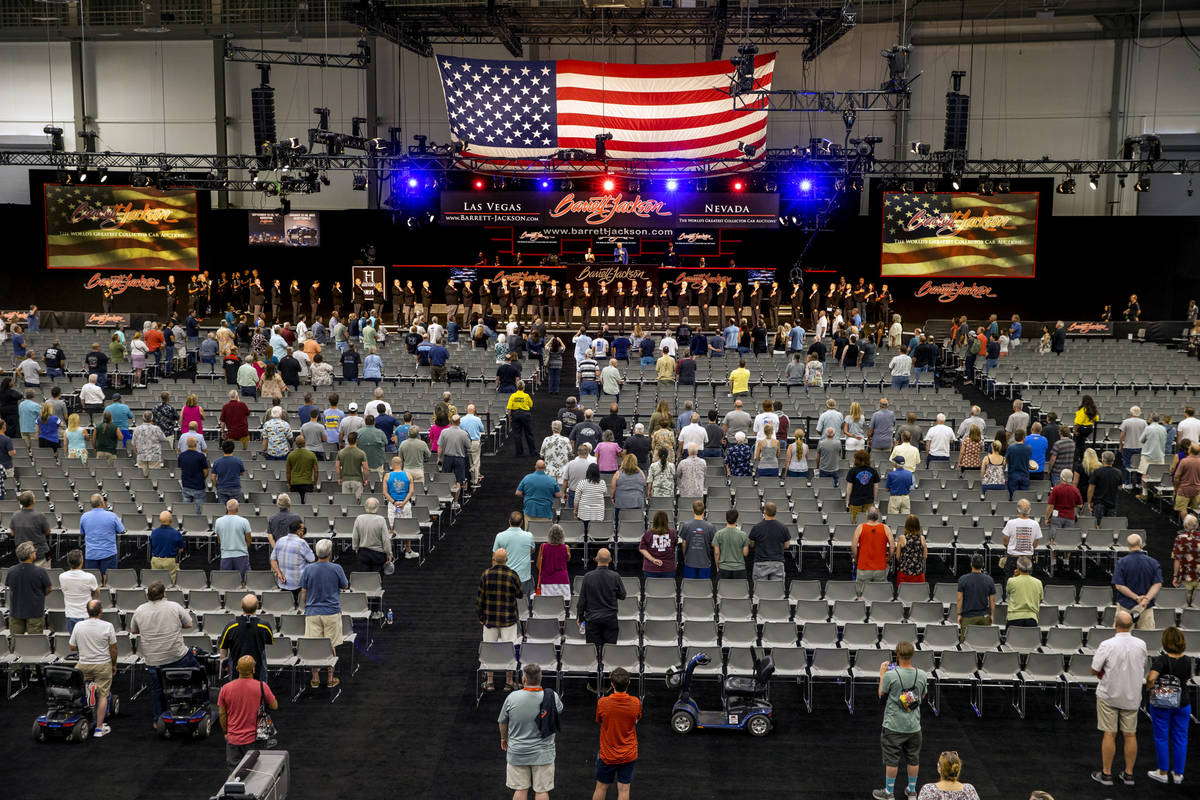Barrett-Jackson employees stand along with attendees for the National Anthem before the collect ...