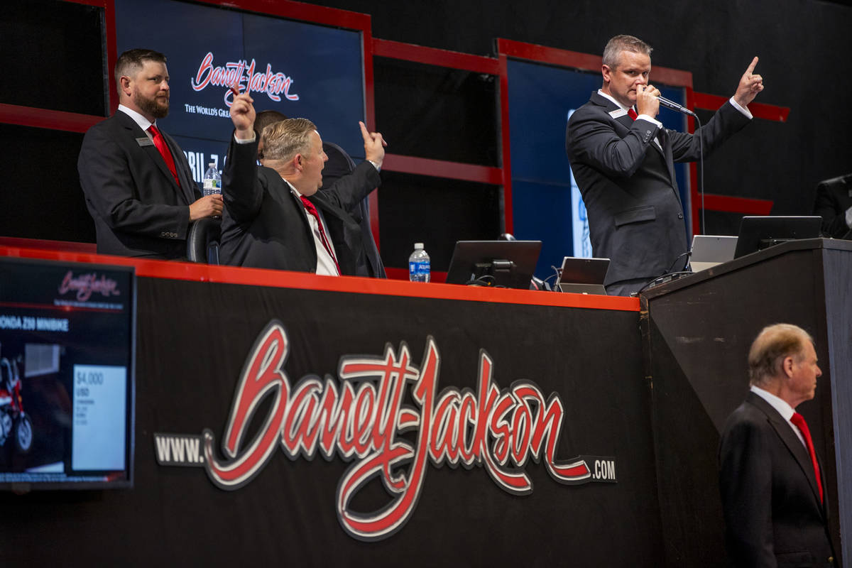 Auctioneer Seth Andrews, right, calls out the final bid on the front podium during the Barrett- ...