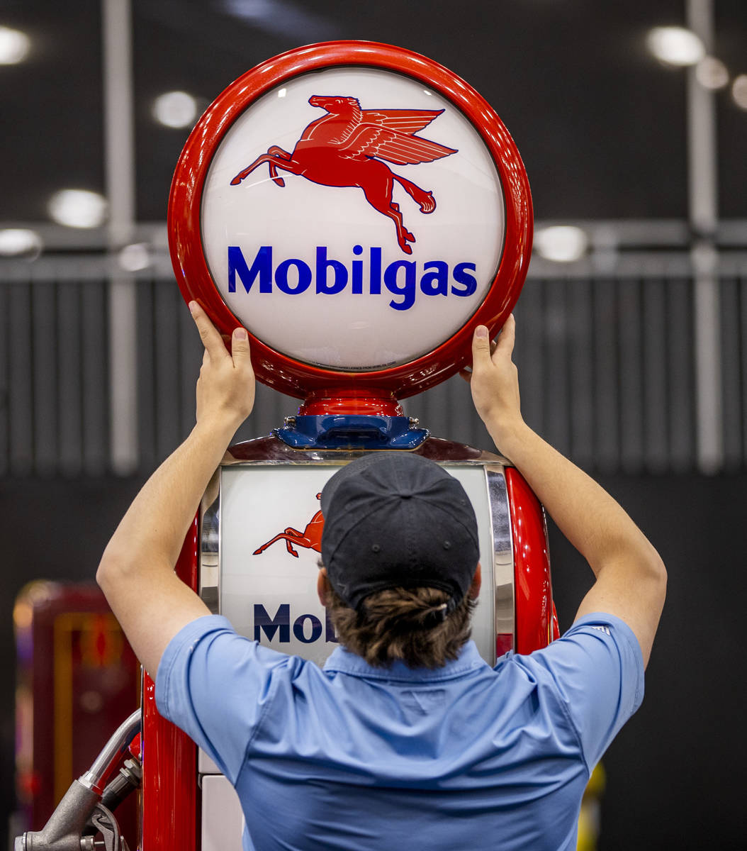 An employee adjusts the lamp atop of a gas pump sold during the Barrett-Jackson collector car a ...