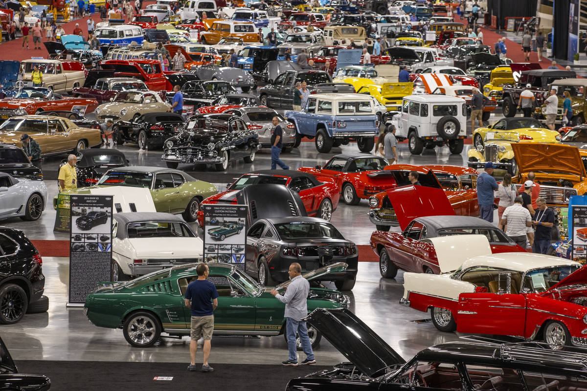 Attendees walk about some of the numerous cars already sold and still up for bid during the Bar ...