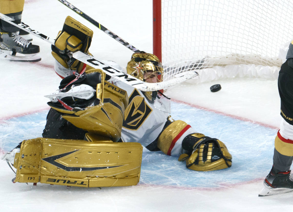 Vegas Golden Knights goaltender Marc-Andre Fleury lies on the ice with the puck in the net on a ...
