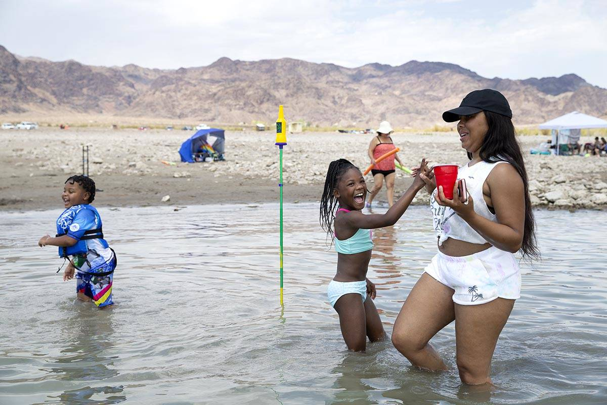 Damisha Simril, right, high-fives her daughter Jaki Walker, 8, after she made her mark in a gam ...