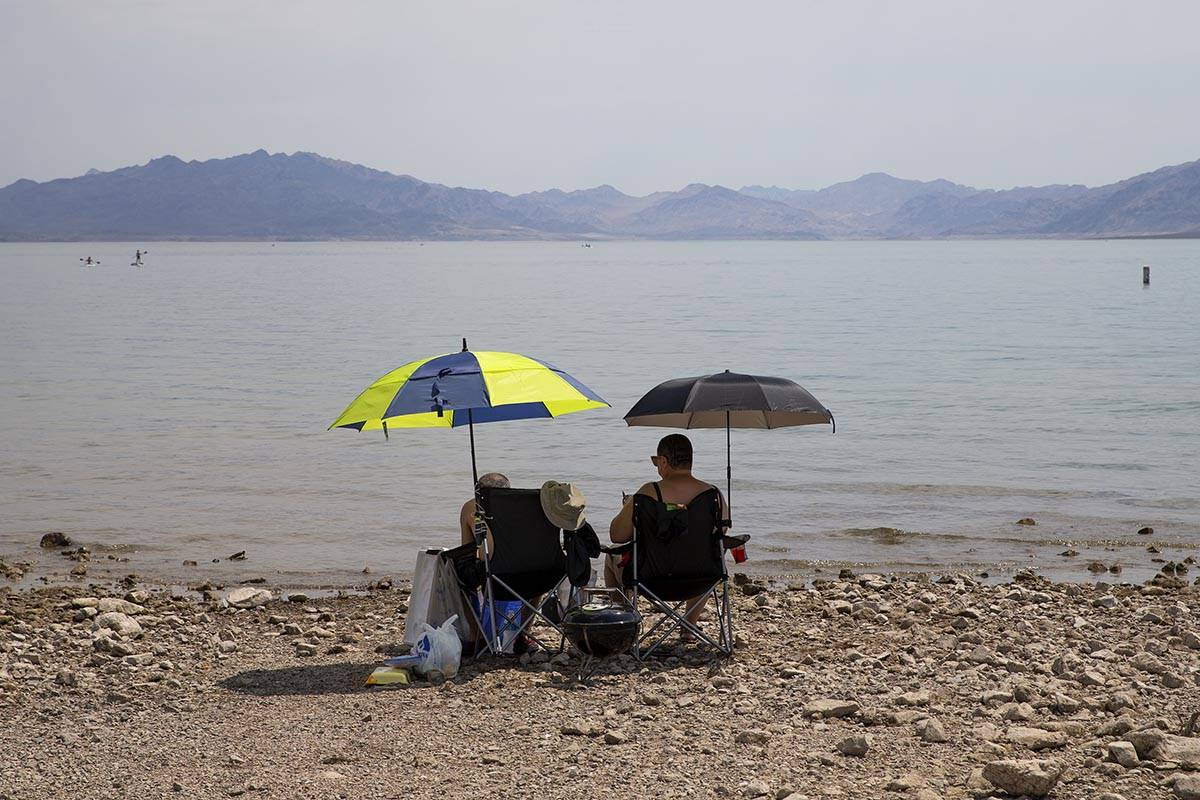 Beach-goers shade themselves under umbrellas along Boulder Beach at Lake Mead on Saturday, June ...