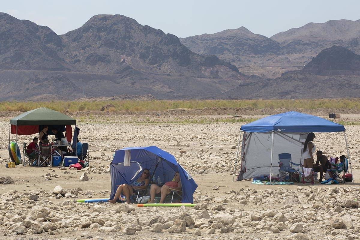 Beach-goers shade themselves along Boulder Beach at Lake Mead on Saturday, June 19, 2021, near ...