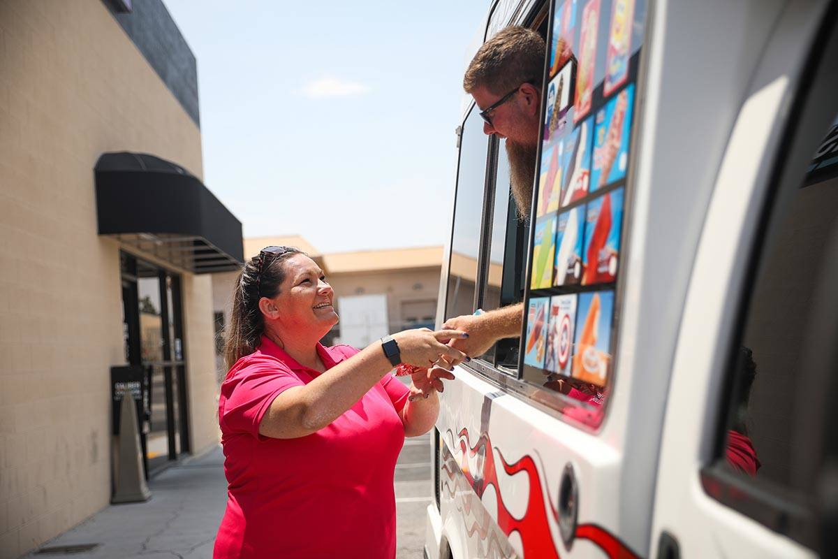 Al Davis, owner of Fat Daddys Ice Cream truck, hands ice cream to Kristan Hall outside Caliber ...