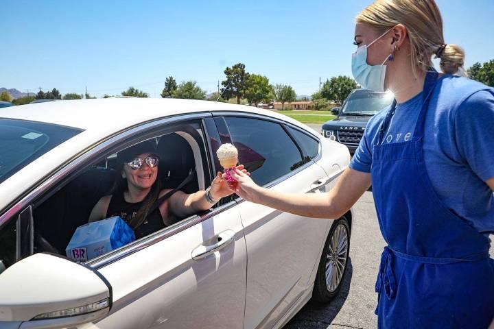 Grace Sanchez hands an ice cream to Danielle Pellinger outside Baskin Robbins in Henderson, Sun ...