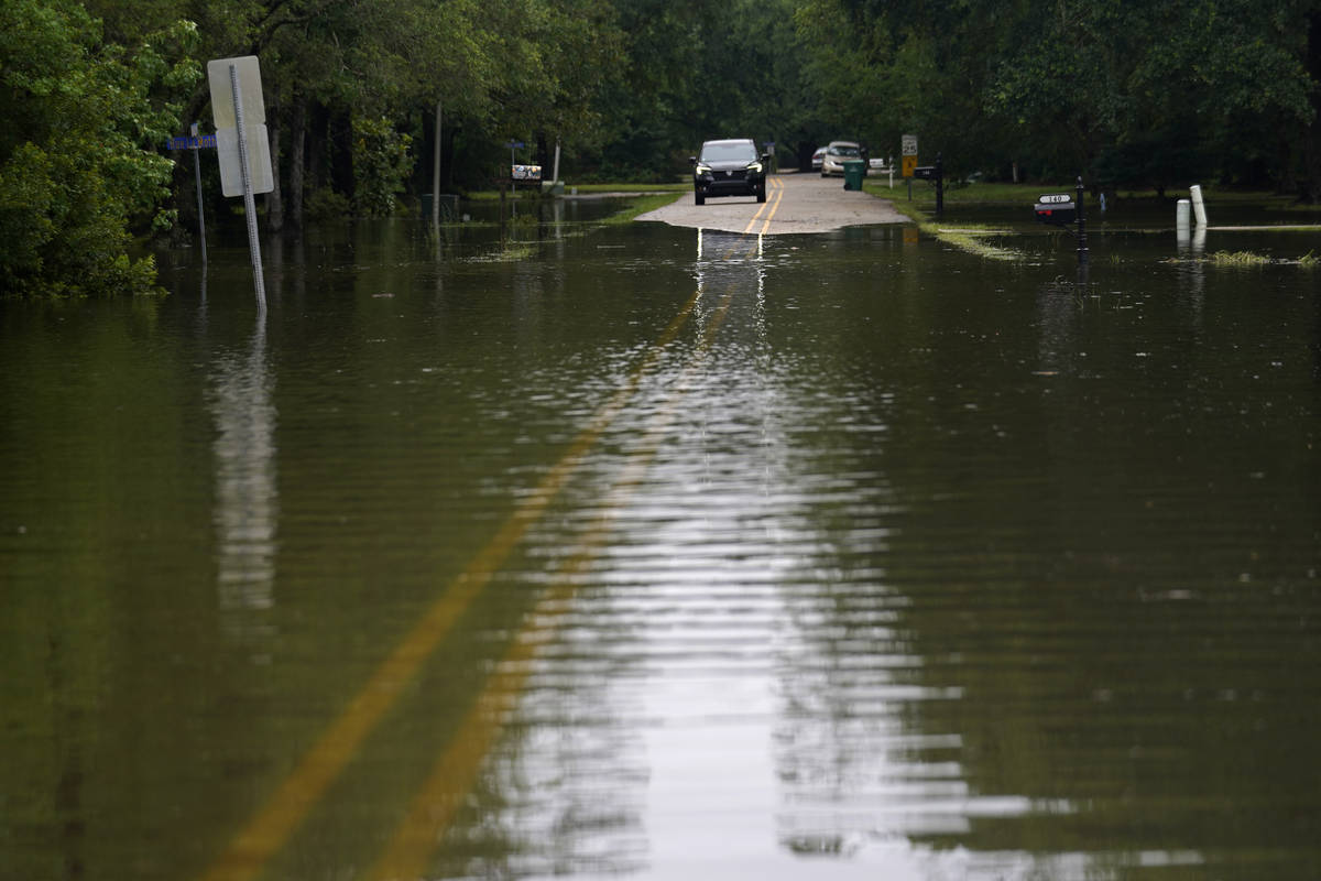 A car stops in front of neighborhood flooding after Tropical Storm Claudette passed through, in ...