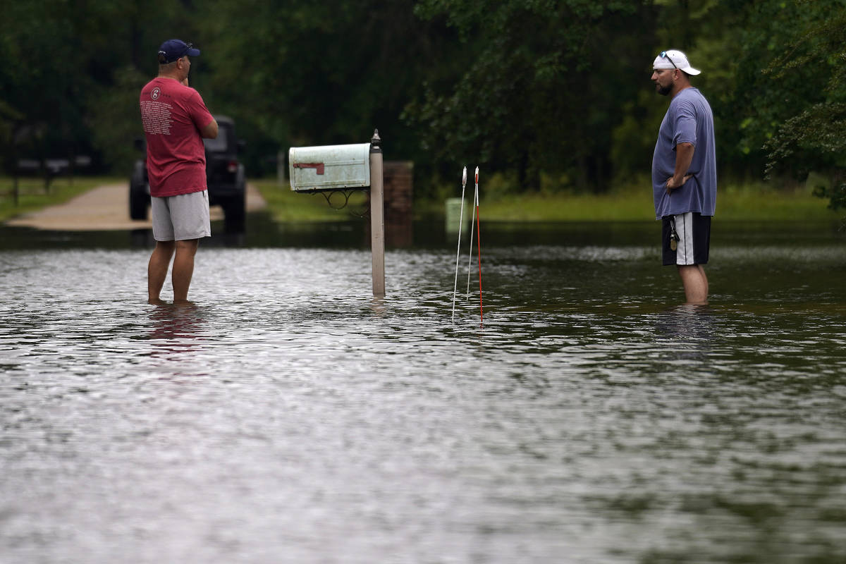 Danny Gonzales, right, stands in front of his flooded house with his neighbor Bob Neal, upset w ...