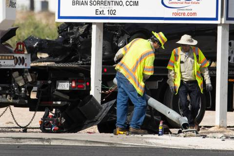 Workers remove a damaged traffic light after a multivehicle crash at the intersection of Warm S ...