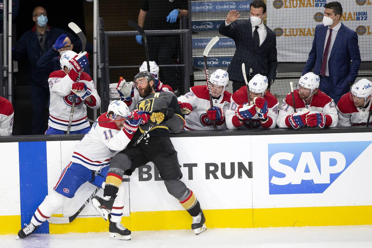 Golden Knights defenseman Alex Pietrangelo (7) is slammed against the boards by Canadiens right ...