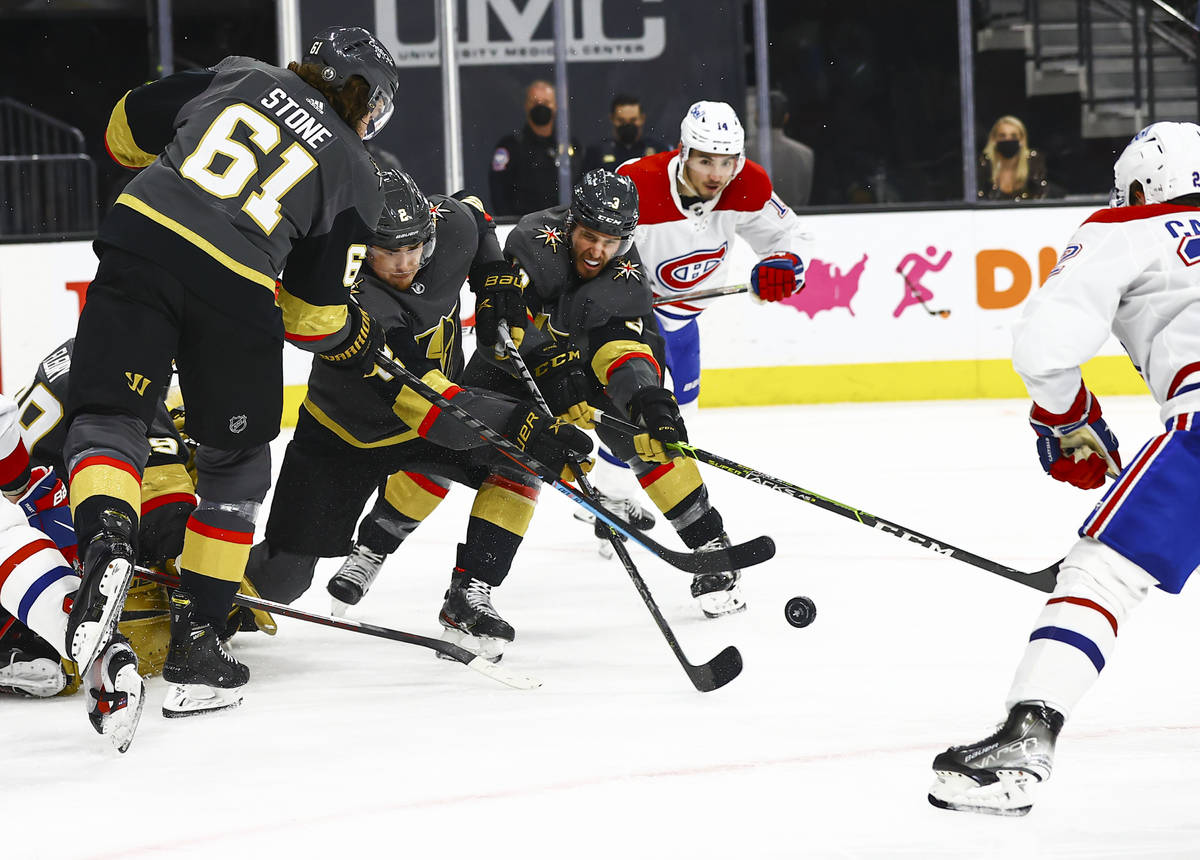 Golden Knights defensemn Zach Whitecloud (2) and Brayden McNabb (3) clear the puck against the ...