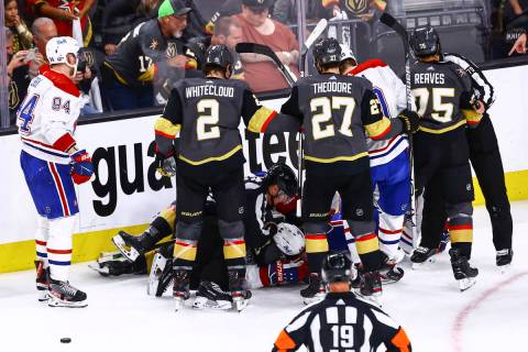 A referee tries to break up a fight between the Golden Knights and Montreal Canadiens during th ...