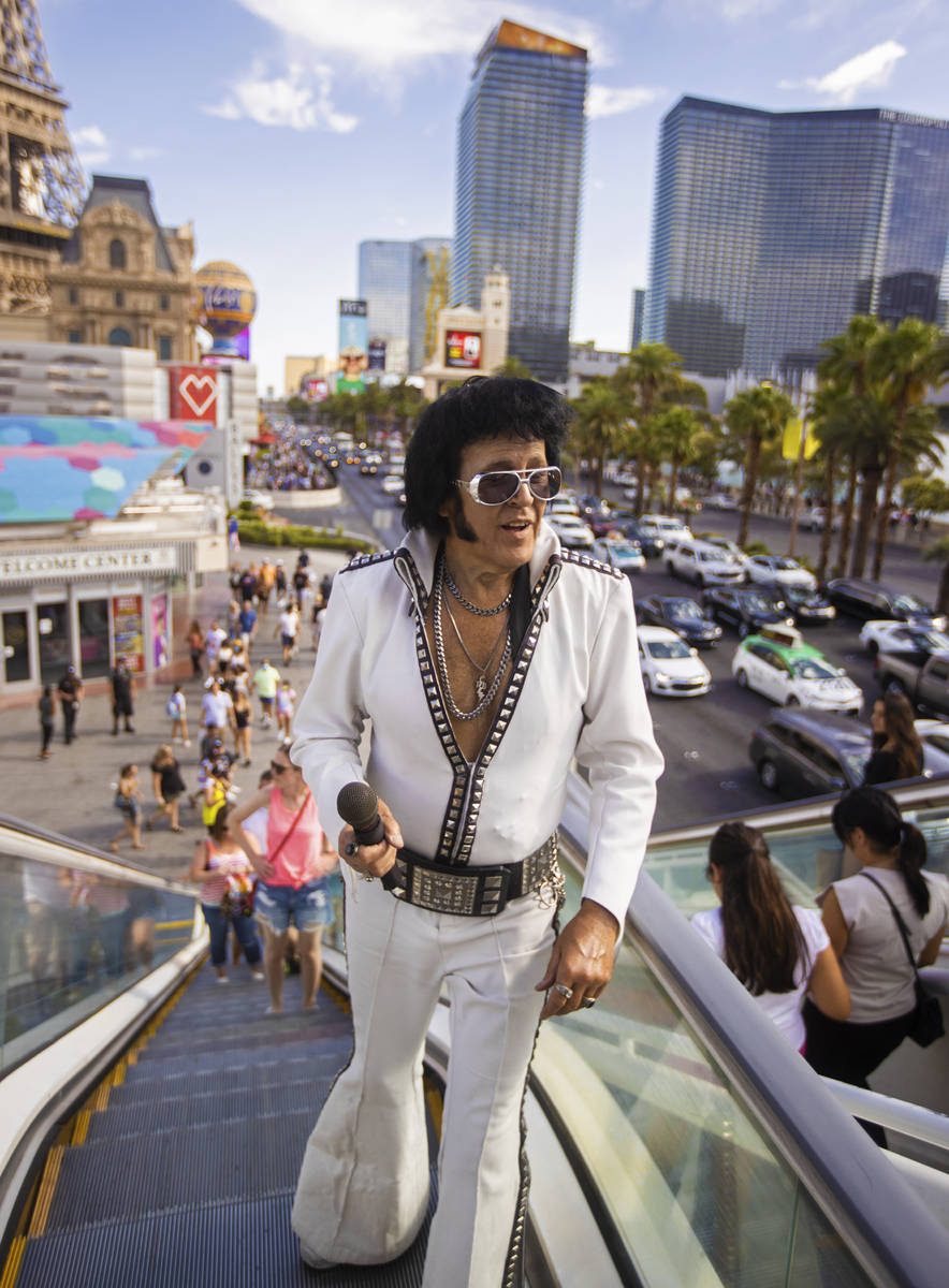 """Chris Johnson, known as """"Counterfeit Elvis,"""" makes his way up the escalator on the Strip during ..."""