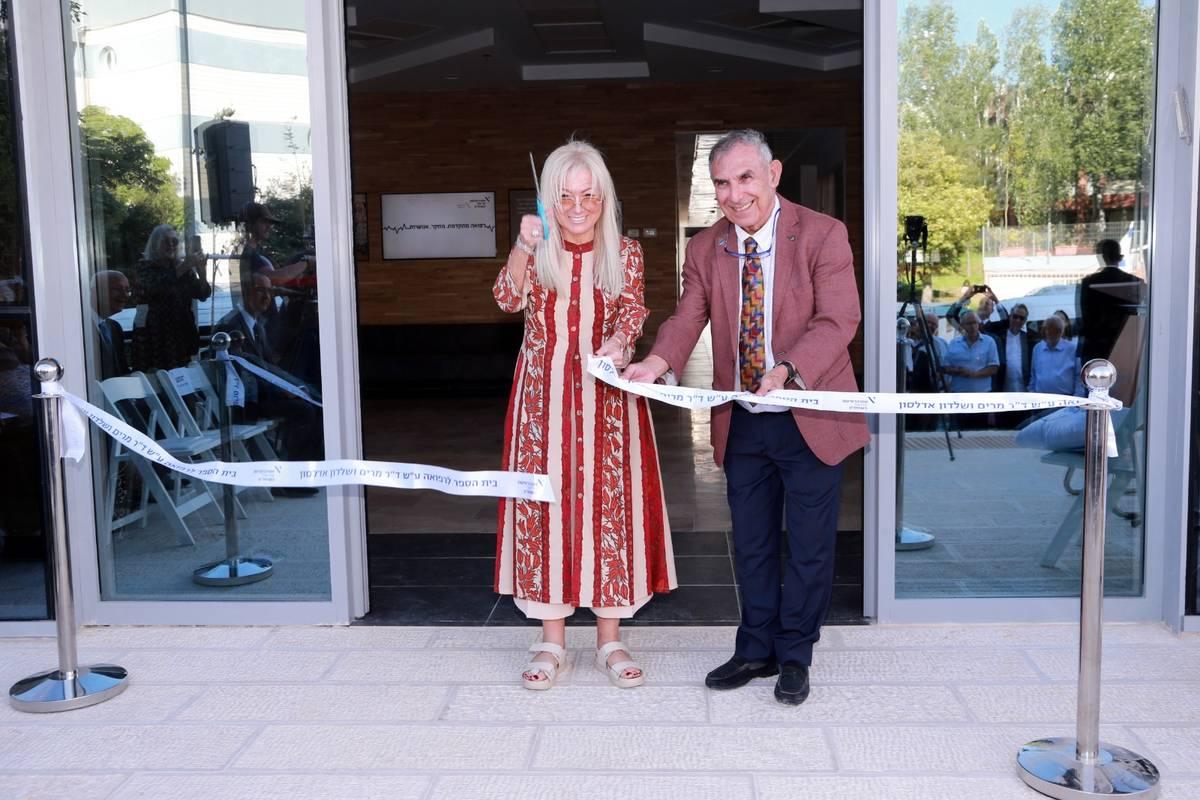 Dr. Miriam Adelson cuts a ribbon with Professor Yehuda Shoenfeld, president of Ariel University ...