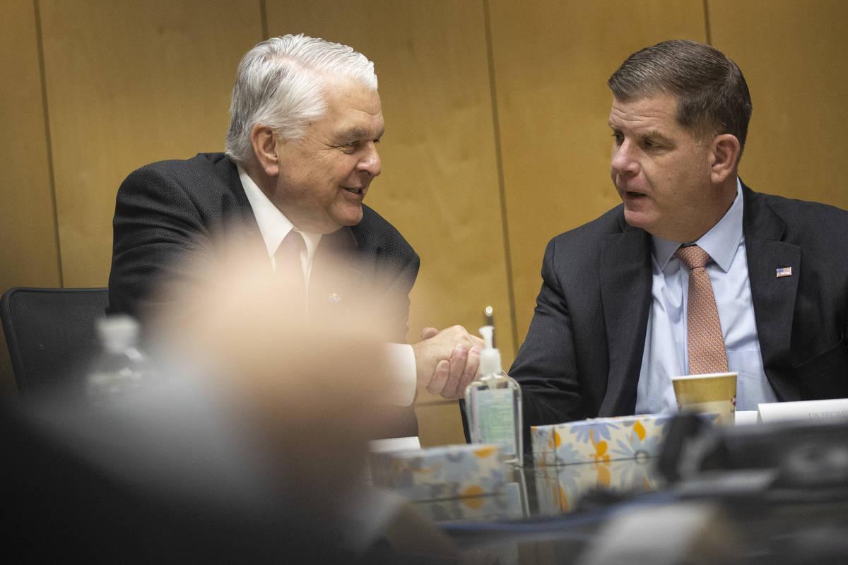 Nevada Gov. Steve Sisolak, left, and U.S. Labor Secretary Marty Walsh, shake hands during a rou ...