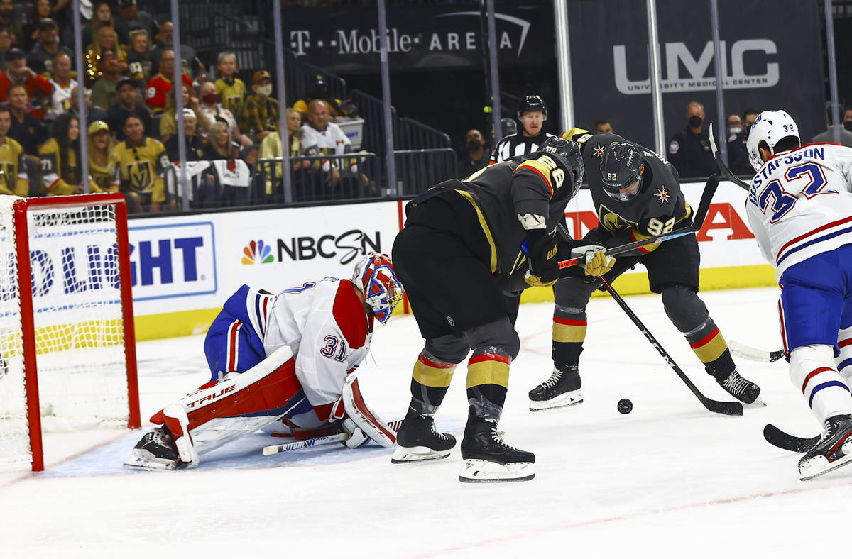 Golden Knights' William Carrier, second from left, and Tomas Nosek (92), try to get the puck i ...
