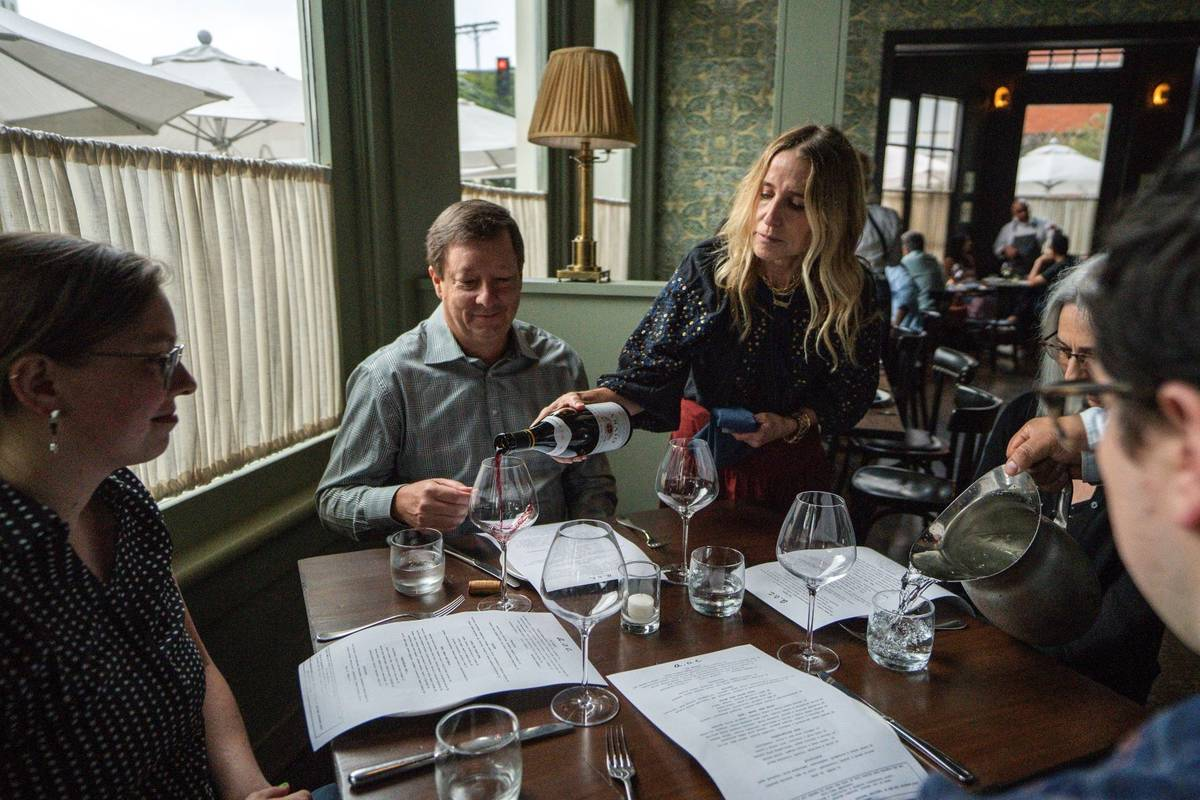 Caroline Styne, owner and wine director at The Lucques Group, serves wine to attorney Alec Nede ...
