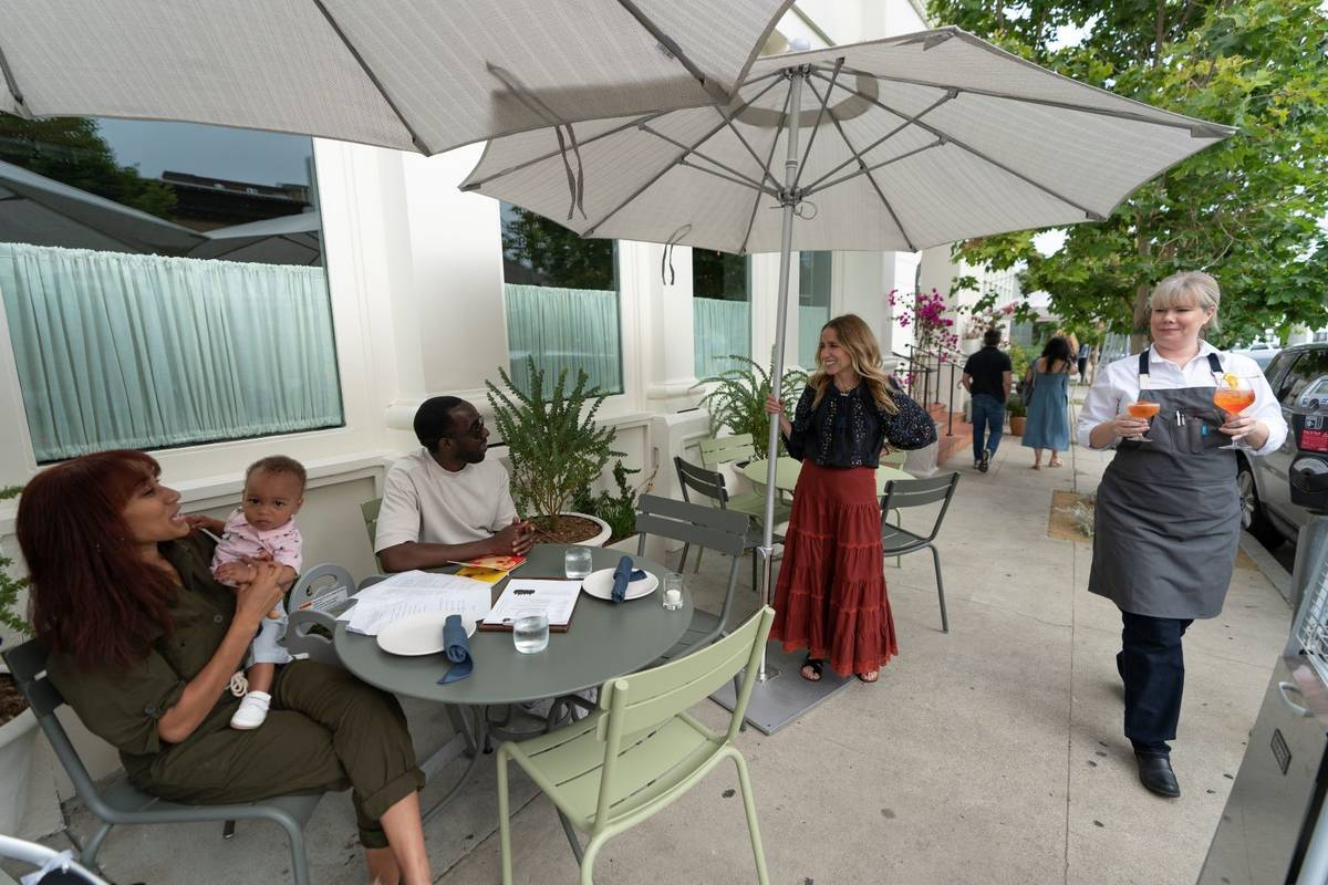 Caroline Styne, owner and wine director at The Lucques Group, standing under umbrella, welcomes ...