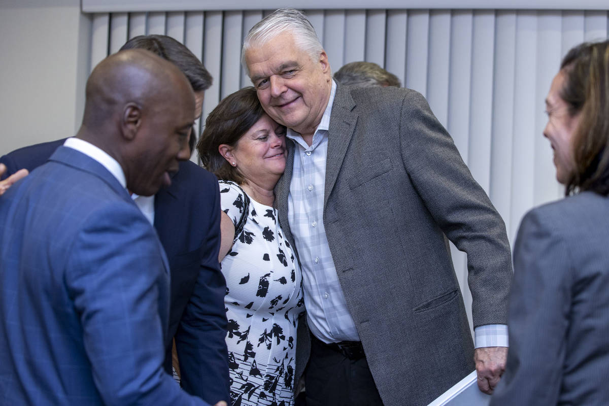 Gov. Steve Sisolak hugs Betsy Fretwell about others during the Nevada COVID-19 Response, Relief ...