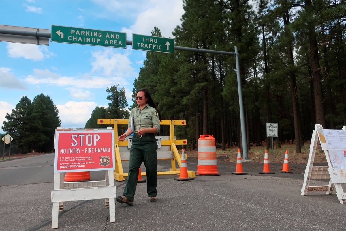 Coconino National Forest employee Amber Wong checks on the road signs outside Flagstaff, Ariz., ...
