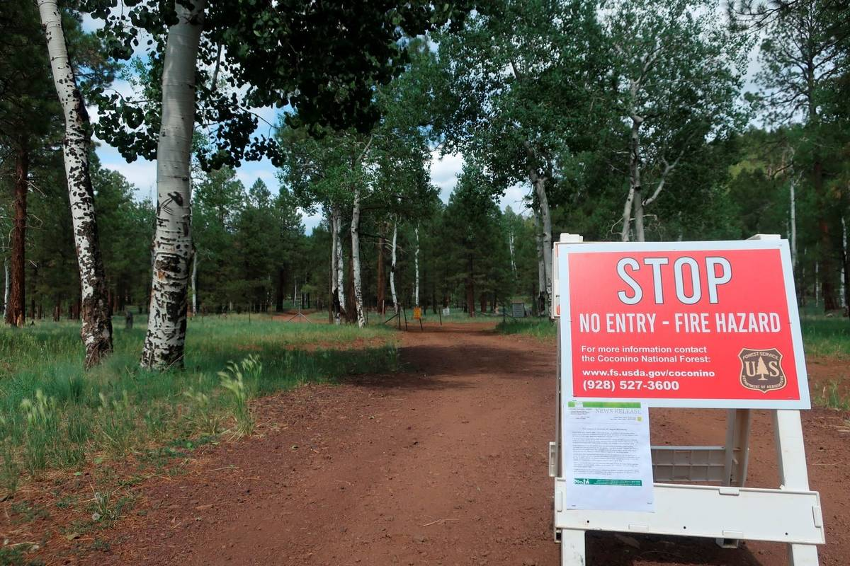 A sign posted ahead of a forest road announces the closure of the national forest surrounding F ...