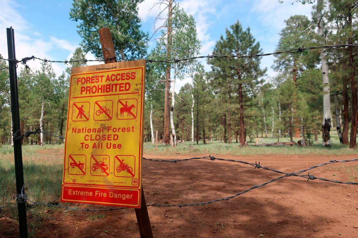 A sign warning of the closure of the national forest surrounding Flagstaff, Ariz., hangs on bar ...