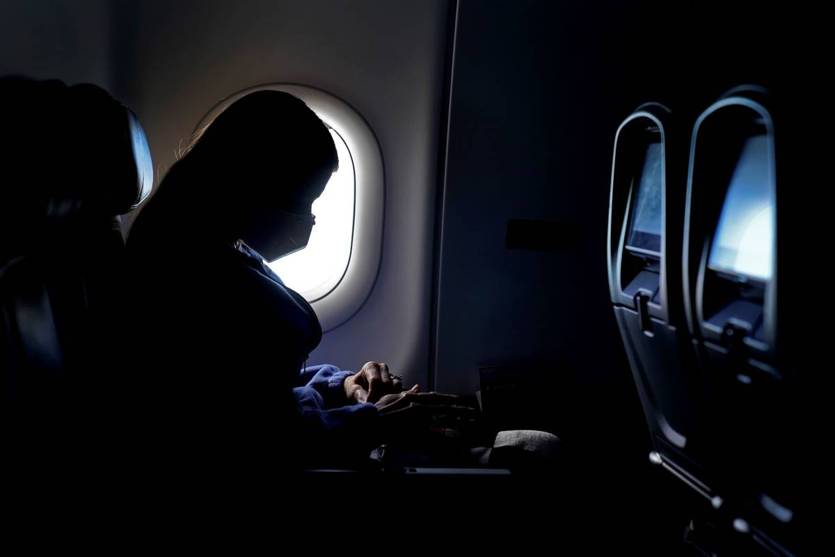 A passenger wears a face mask she travels on a Delta Air Lines flight after taking off from Har ...