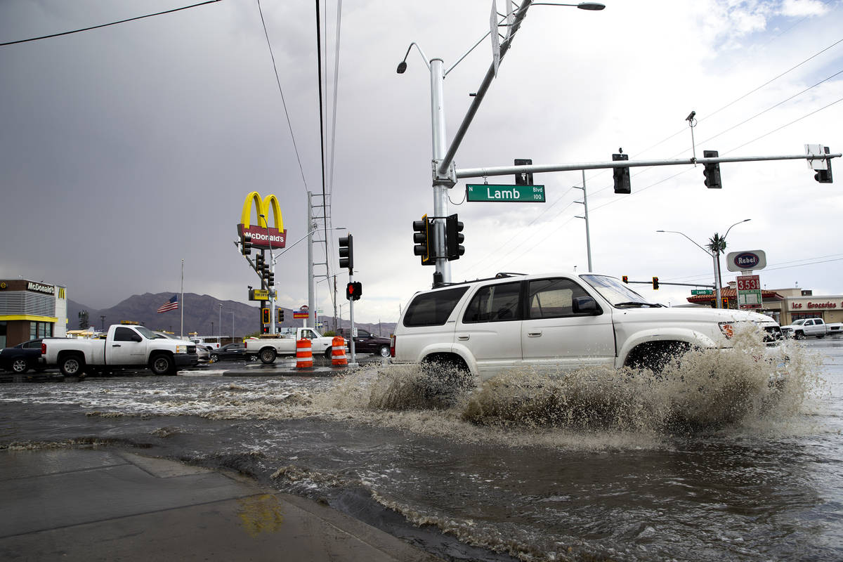 Motorists make way through flooding at the intersection of South Lamb Boulevard and East Charle ...