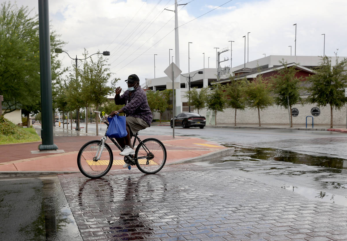 A cyclist who gave his name as Prophet rides after a light rain on 7th Street at Gass Avenue in ...