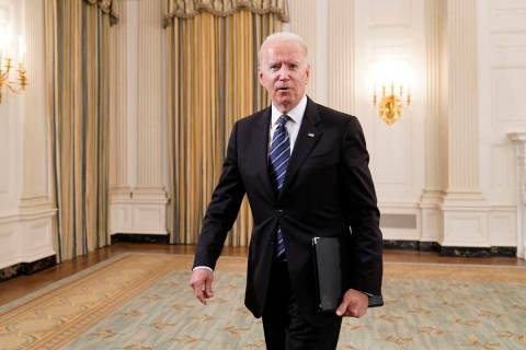 President Joe Biden walks out of the State Dining room after an event with Attorney General Mer ...