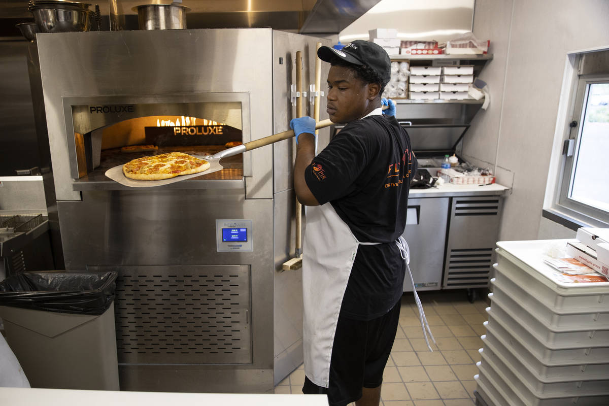 Crew member Derald Williams trains in the kitchen of the Fly Pie pizza drive-thru at the inters ...