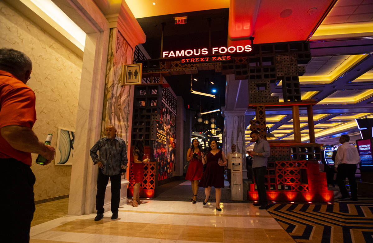 People walk by an entrance to the Famous Foods Street Eats area during the opening night of Res ...