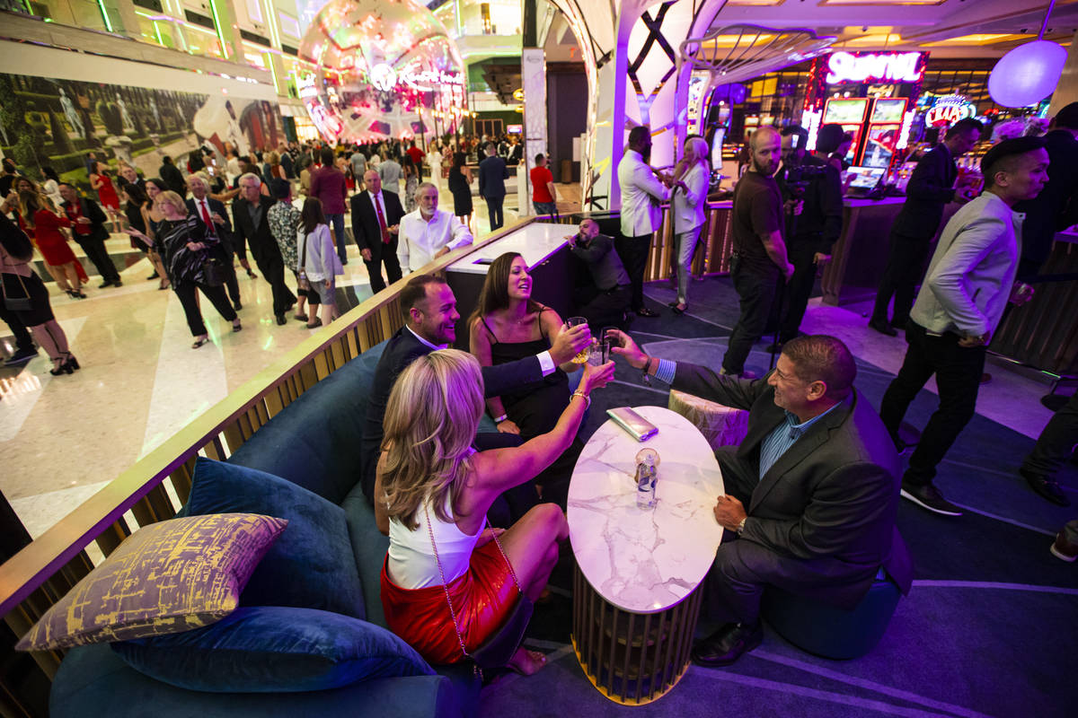 People toast and mingle at GatsbyÕs cocktail lounge during the opening night of Resorts Wo ...