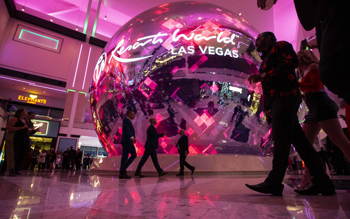 People walk by the illuminated sphere in The District during the opening night of Resorts World ...