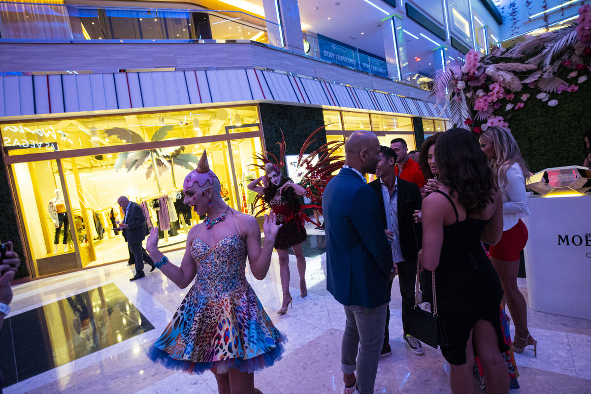 Costumed performers entertain the crowd in The District during the opening night of Resorts Wor ...