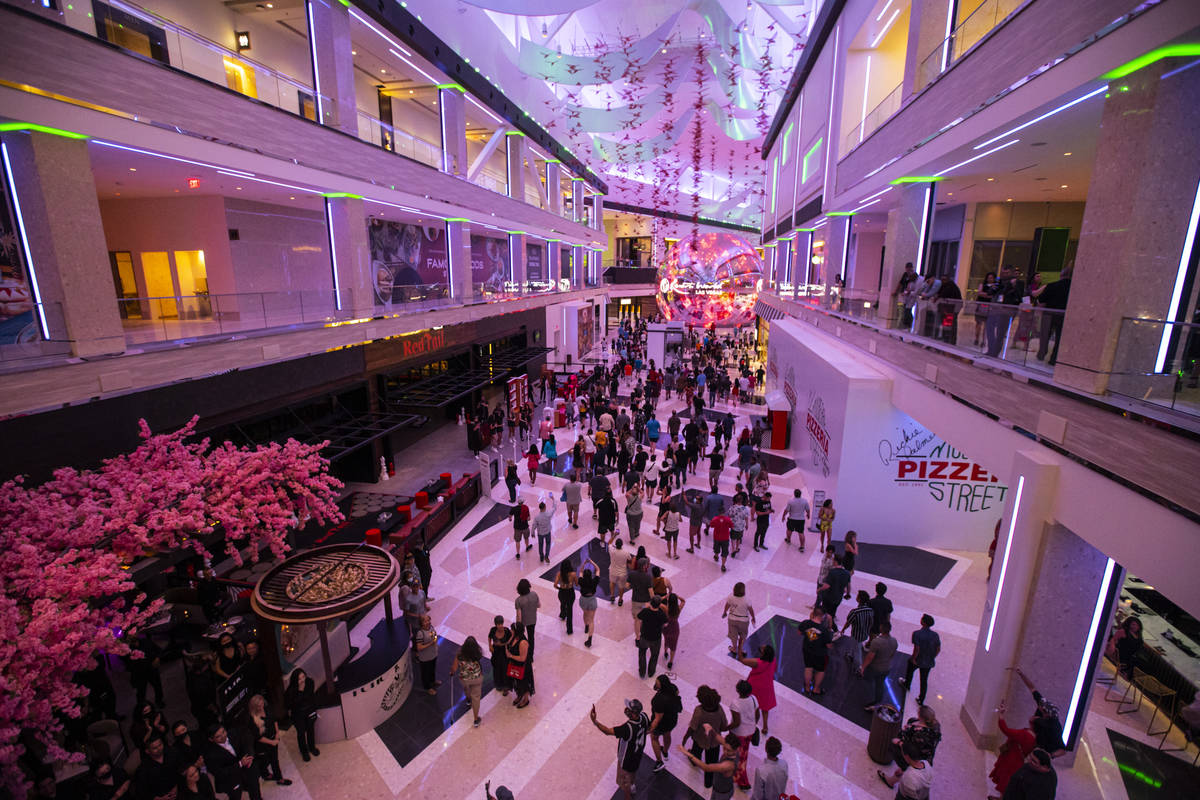 People walk into The District as the doors open to the public at Resorts World Las Vegas on Thu ...