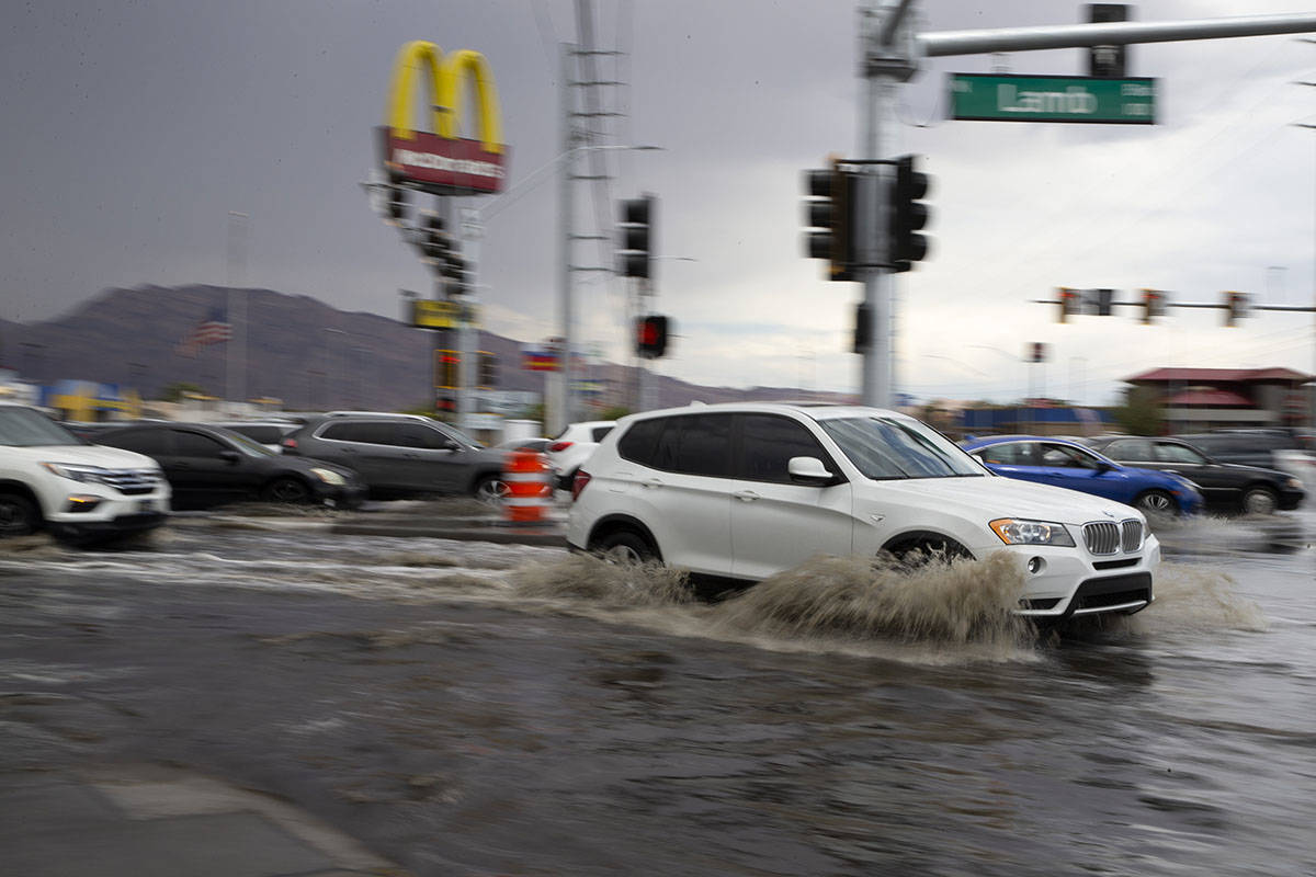 Motorists drive through flooding at the intersection of South Lamb Boulevard and East Charlesto ...