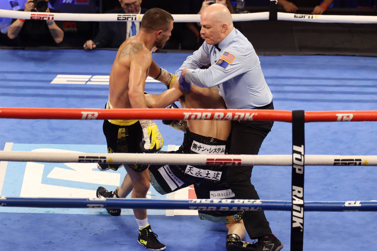 Vasyl Lomachenko, left, looks as the referee steps in to stop the fight against Masayoshi Nakat ...