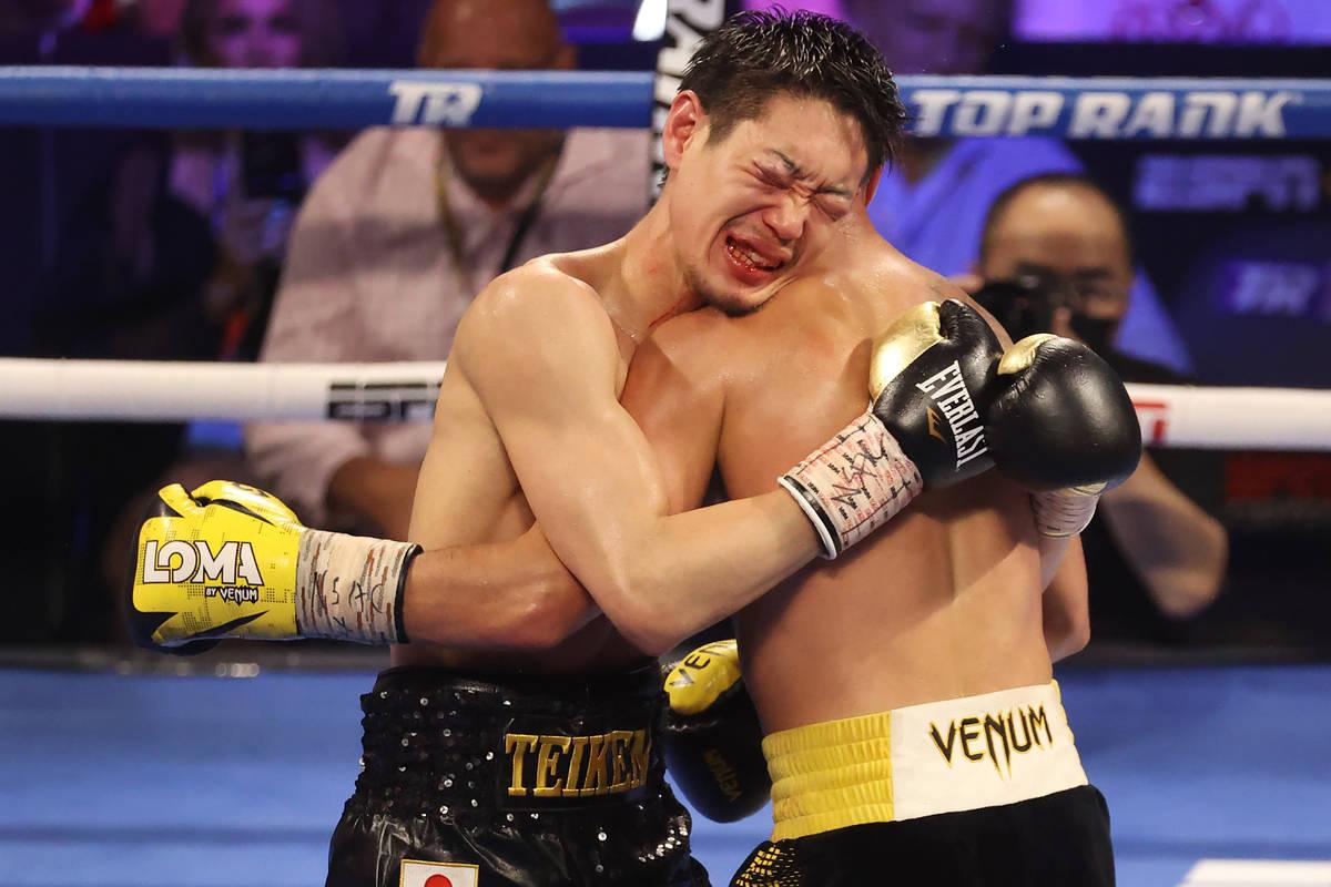 Masayoshi Nakatani, left, holds on to Vasyl Lomachenko in the ninth round of the lightweight bo ...
