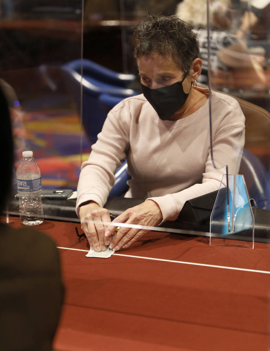 Jan Fisher of Las Vegas, co-host of 2021 Nevada State Ladies Poker Championship, checks cards d ...